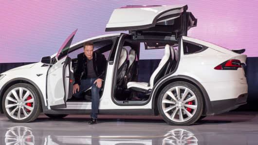 Elon Musk, chairman and chief executive officer of Tesla Motors, exits the Model X sport utility vehicle during an event in Fremont, California, Sept. 29, 2015.