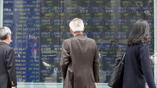 Japanese stocks have been in focus of late, with the yen's strength against the dollar hurting major exporters. Here pedestrians take a look at an electronic stock quotation board at the window of a securities company in Tokyo.