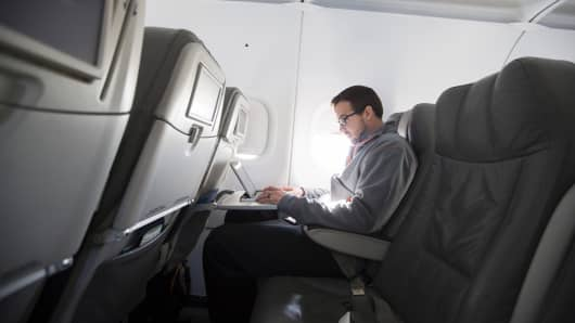 A man uses his laptop on an airline flight.
