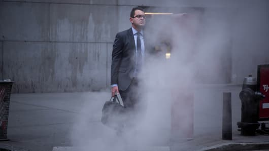 A man walks through steam coming from a man hole on Wall Street near the New York Stock Exchange (