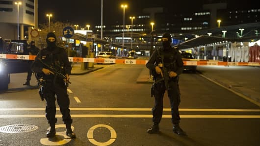 Dutch policemen stand guard by a cordoned off area outside Amsterdam's Schiphol Airport late on April 12, 2016