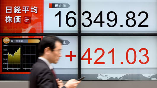 A businessman walks past an electric quotation board flashing the Nikkei key index of the Tokyo Stock Exchange (TSE) in front of a securities company in Tokyo on April 13, 2016.