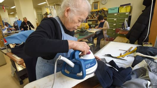 Workers repair clothes at a seniors' work center in Tokyo. Japan's rapidly aging population is already taking a toll on its labor force, according to many economists and institutions.