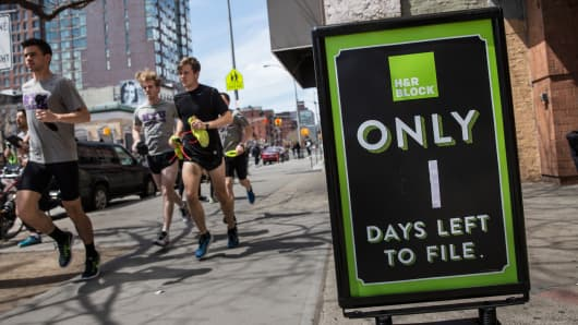 A group of men run past an H&R Block on April 15, 2015 in New York City.