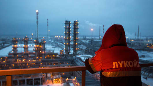 An employee looks out over the illuminated petroleum cracking complex at the Lukoil-Nizhegorodnefteorgsintez oil refinery in Russia.