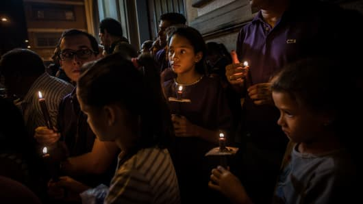 People walk down a dark street, holding candles as they pass closed shops and offices, during a Holy Week procession in eastern Caracas, Venezuela.