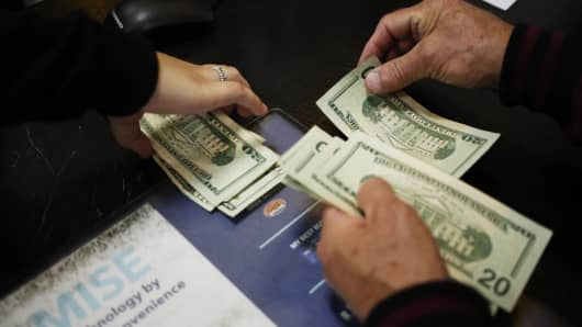 A shopper counts U.S. dollar banknotes at a checkout counter