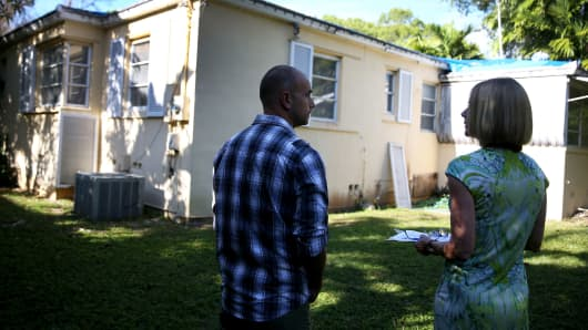 A prospective home buyer, left, is shown a  home by a real estate agent in Coral Gables, Florida.