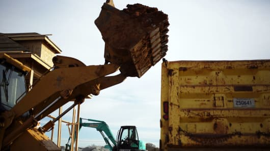 A Caterpillar 953C track loader moves soil to a dump truck as contractors work during the construction of residential housing in the Norton Commons subdivision in Louisville, Kentucky.