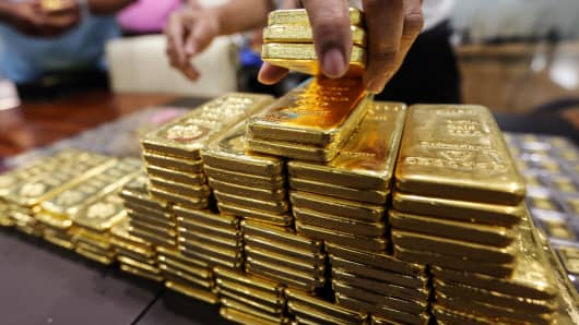 An employee arranges one kilogram gold bars for a photograph at the YLG Bullion International Co.