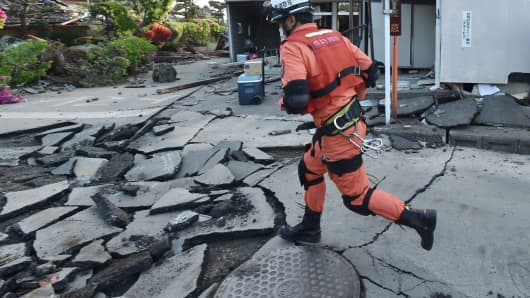 A member of a rescue team runs on a street cracked by the earthquake in Mashiki, Kumamoto prefecture on April 16, 2016.