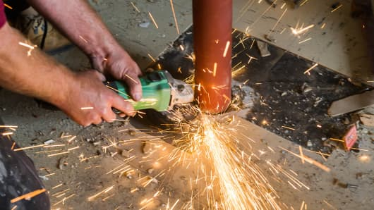A construction worker using an angle grinder to cut a metal pipe.