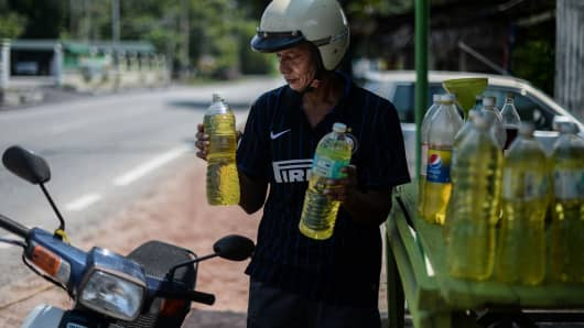 A villager carries bottles of petrol oil at a village in Hulu Langat, outside Kuala Lumpur on April 18, 2016. Oil prices plunged on April 18 after the world's top producers failed to reach an agreement on capping output aimed at easing a global supply glut, sparking fears it could set off another round of price.