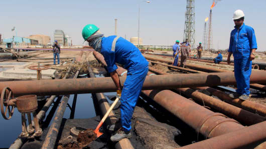 Men work at Al-Sheiba oil refinery in the southern Iraq city of Basra, April 17, 2016.