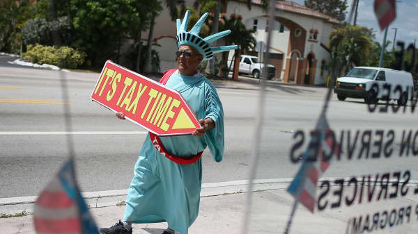 Armando La Rosa directs people to the Liberty Tax Service office as the deadline to file taxes looms on April 15, 2016 in Miami, Florida. The Internal Revenue Service moved the deadline from April 15th to Monday the 18th due to the Emancipation Day holida
