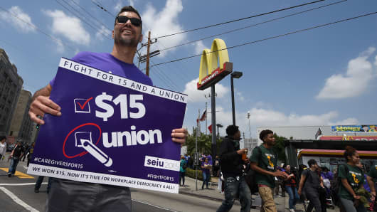 Workers from the fast food, home care and child care industries protest outside a McDonald's as they demand a nationwide $15-an-hour minimum wage, in Los Angeles on April 14, 2016.