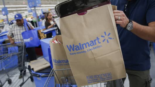 A customer puts a bag of purchases into a shopping cart at a Wal-Mart Stores Inc. location in Los Angeles.