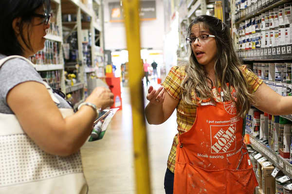 A Home Depot employee, helps a shopper at the store in Miami.