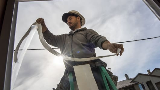 A contractor applies weather stripping to a window on a home under construction at the Toll Brothers housing development in San Ramon, California.