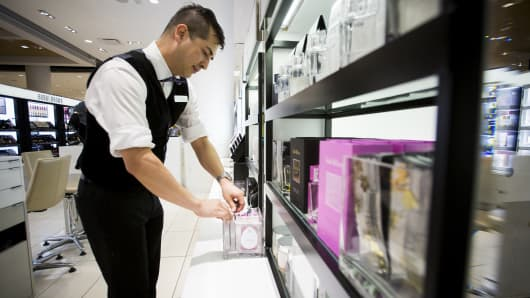 An employee arranges cosmetic products in a container in a Nordstrom Inc. store