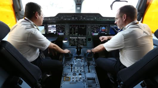 Pilots inside the cockpit aboard a Qatar Airways Airbus A350 XWB aircraft at the Singapore Airshow on February 16, 2016