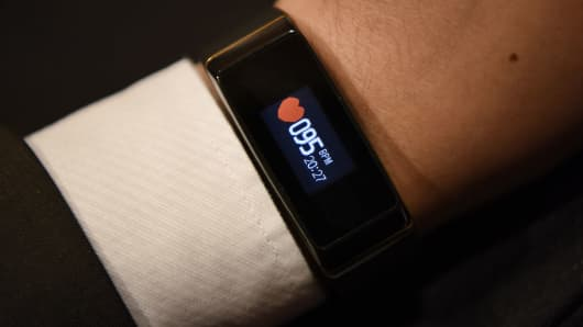 An exhibitor displays a 3Plus Activity Tracker for a photograph during ShowStoppers at the 2016 Consumer Electronics Show  in Las Vegas, Nevada on Jan. 6, 2016. Activity trackers have become one of the most popular forms of wearable devices today, collecting a host of data about the wearer.