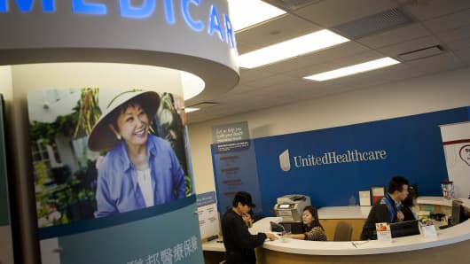 Cusomers get information from a reception desk at a UnitedHealthcare store