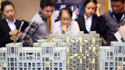 Customers and realtors look at building models at an exhibition in Jiashan in East China.