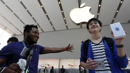 A customer, right, shows his Apple Inc. iPhone SE after purchasing it at the company's Omotesando store on March 31, 2016 in Tokyo, Japan.