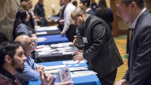 Job seekers, right, speak with recruiters at the San Jose Career Fair in California.
