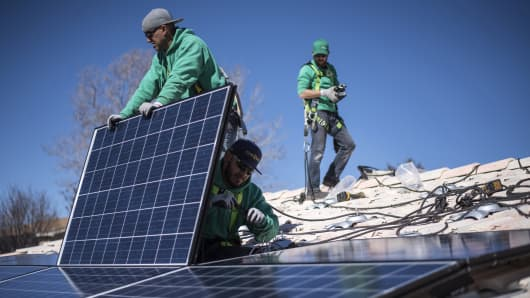 Workers secure solar panels to a rooftop during a SolarCity Corp. residential installation in Albuquerque, N.M.