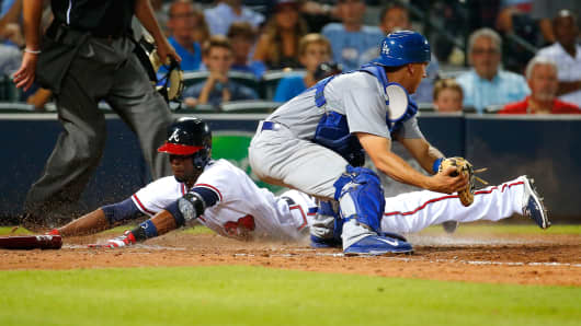 Pedro Ciriaco #13 of the Atlanta Braves scores as he slides safely over homeplate past Austin Barnes #65 of the Los Angeles Dodgers in the sixth inning on a two-RBI single hit by Jace Peterson #8 at Turner Field on July 20, 2015 in Atlanta, Georgia.