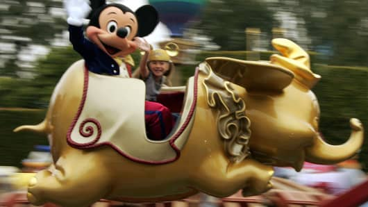 Mickey Mouse (L)rides on a golden Dumbo with Caroline Sunshine age nine, on the Disney 50th anniversary press preview day at Disneyland in Anaheim, CA,