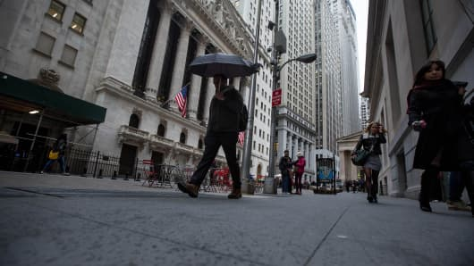 A pedestrian carries an umbrella while walking past the New York Stock Exchange.