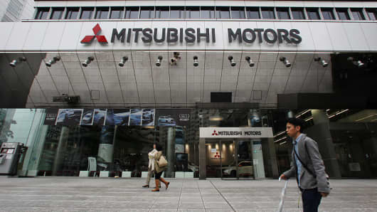 Pedestrians walk past the Mitsubishi Motors Corp. headquarters in Tokyo, Japan, on Thursday, April 21, 2016. Mitsubishi Motors' disclosure that it manipulated fuel-economy tests has seen its share prices plunge in recent sessions.
