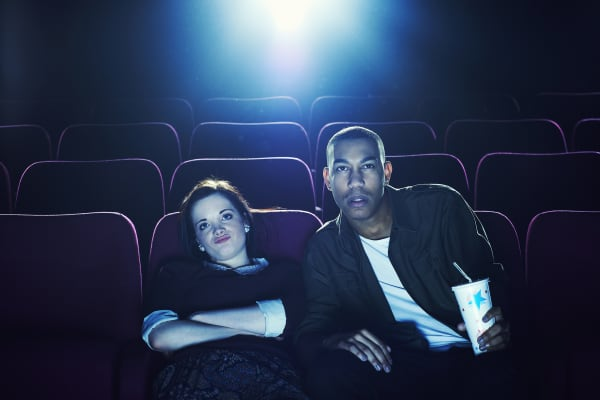 Skeptical couple in movie theater