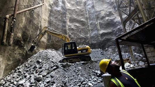 A worker operates a Caterpillar Inc. hydraulic excavator during the final stage of construction on the Tunnel Rio 450 project in Rio de Janeiro, Brazil.