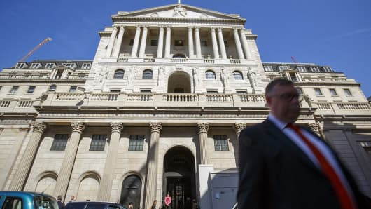 Members of public walk past the Bank of England in London, England