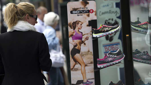 A pedestrian walks past a display of Skechers shoes.