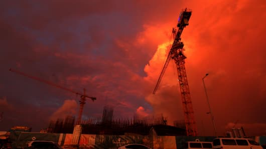 Cranes stand still at sunset in October 2015, on the site of a new, Chinese-built hotel in Colombo. A new Sri Lankan government suspended support for a number of Chinese projects in 2015, including the capital's Port City mega-development.