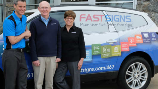 (Left) Michael Gilpin, co-owner of FASTSIGNS, with his parents, co-owners Kim and Judy Gilpin