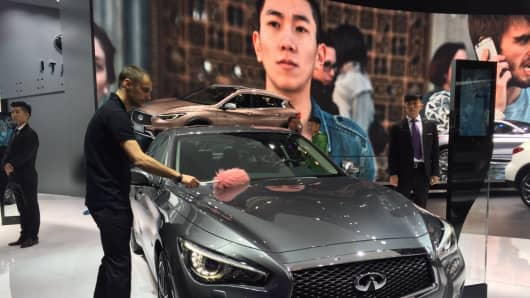 An attendant dusts a Q50 L on display at Infiniti's stand at the Beijing Auto Show. Infiniti is the luxury vehicle division of Japan's Nissan.