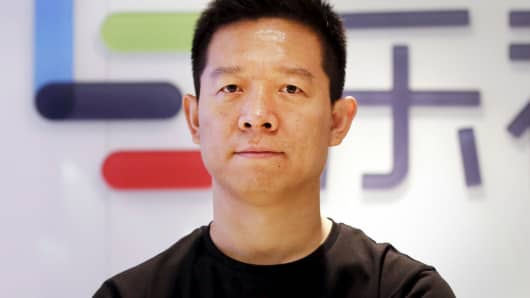 Jia Yueting, co-founder and head of Le Holdings Co Ltd, also known as LeEco and formerly as LeTV, poses for a photo in front of a logo of his company in Beijing.