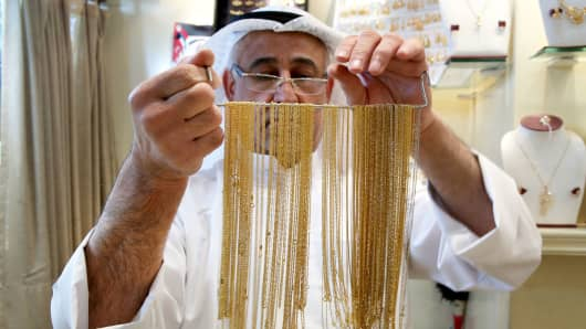 A Kuwaiti jeweler displays gold necklaces at his shop in downtown Kuwait City on March 18, 2016.