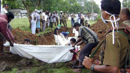 Workers bury the bodies of 41 suspected Tamil Tiger fighters recovered by the government after fighting in the northern district of Vavuniya in January 2009.