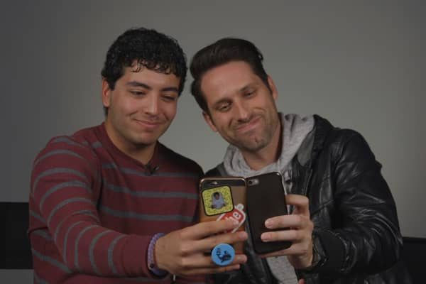 Aaron Martinez (left) and David Rhodes take selfies with their phones.