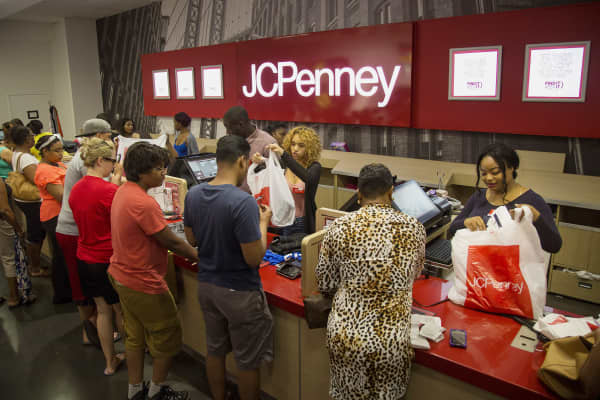 Employees assist customers at the checkout counter of a J.C. Penney store.