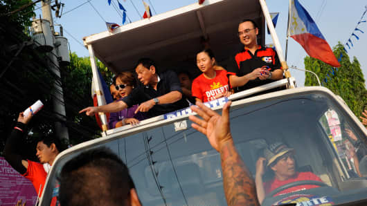 Philippine presidential candidate Rodrigo Duterte (L) gestures to the crowd during a campaign motorcade on April 27, 2016 in Manila. The brash, tough-talking mayor of Davao on the southern island of Mindanao has been the surprise pre-election poll favorite pulling away from his rivals despite controversies. Duterte has shocked the political establishment with his unorthdox style of campaigning and his profanity-laced campaign speeches.