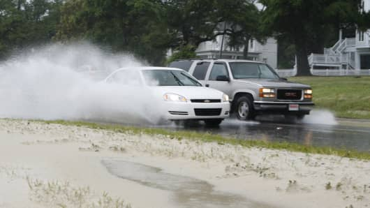 Cars spray water pushed onto U.S. Highway 90 in Biloxi, Mississippi