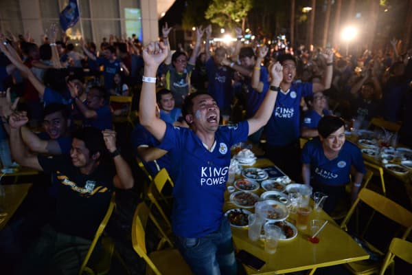 Thai Leicester City football supporters celebrate the team's victory against Swansea FC as they watch a live broadcast on April 24, 2016 in Bangkok. Leicester City's unlikely surge to the top of the Premier League is 'good for football', the club's billionaire Thai backers said after April 24, 2016's mauling of Swansea. Hundreds of jubilant Thai fans defied the steaming city heat to watch the 4-0 drubbing on a big screen at the headquarters of King Power -- whose name is emblazoned on the club's shirt.
